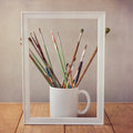 Artist painting brushes on wooden table with picture frame