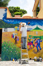 Artist painting outdoor mural on ladder in ajijic mexico Stock Image
