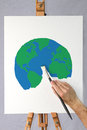 Artist painting a picture of the earth on a canvas Royalty Free Stock Images
