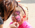 Artist paints on face of little girl Royalty Free Stock Photo