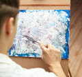 Artist paints palette knife painting on canvas Royalty Free Stock Images