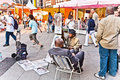 Artist paints portraits in a pedestrian area in vienna austria april man tourists for earning money he shows collection of his Stock Photos