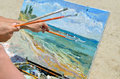 The artist's hand holding a brush, painting the picture Royalty Free Stock Photo