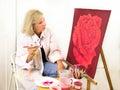Artista studies her painting de uma rosa Fotografia de Stock Royalty Free