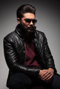 Artistic pose of a dramatic fashion young man with beard wearing leather jacket and sunglasses looking down Stock Image