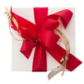 Artistic red bow with gold braid on a gift overhead view of beautiful and balls white box isolated white for christmas Stock Images