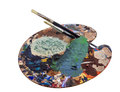 Artists palette paint covered with brushes Royalty Free Stock Photography