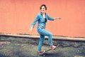 Artsy portrait of a brunette cute girl on a skateboard, laughing and having a good time. Healthy concept of modern life, hipster g