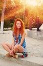 As jovens mulheres de cabelo vermelhas que sentam se no skate com seus pés cruzaram retroiluminado pelo sol Imagem de Stock Royalty Free