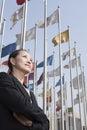 As mulheres de negócios que estão com braços cruzaram se com os mastros de bandeira no fundo Foto de Stock