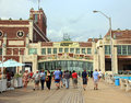 Asbury park boardwalk people walking on the in nj shore next to the convention hall building and the paramount theater Royalty Free Stock Image