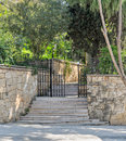 Ascending marble stairs leading to a public park, Stone wall, and fence iron door Royalty Free Stock Photo