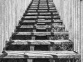 Ascending wooden stairs black and white monochrome image straight on of outdoor with metal rail posts framing evenly on both sides Stock Photos