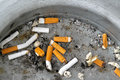 Ashtray cigarette butts discarded in Stock Photos