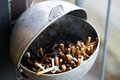 Ashtray full of used cigarettes a disgusting smoked for employers in front a company building Royalty Free Stock Photos