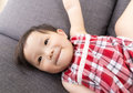 Asia little girl making funny face and lying on sofa Stock Image