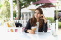 Asia young business woman sitting in a cafe with iced coffee and call phone concept Stock Images