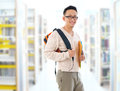 Asian adult student in library southeast casual wear with school bag carrying text books standing inside school building Stock Photography