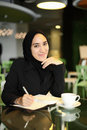 Asian arabic worker cafe young attractive female corporate smiling and writing in her journal at a Royalty Free Stock Photos
