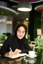 Asian arabic worker cafe young attractive female corporate smiling and writing in her journal at a Stock Photography