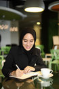 Asian arabic worker cafe young attractive female corporate smiling and writing in her journal at a Stock Photos