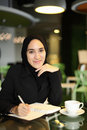 Asian arabic worker cafe young attractive female corporate smiling and writing in her journal at a Stock Images