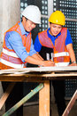 Asian architect and supervisor on building site chinese point a construction plan Royalty Free Stock Photography