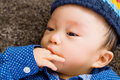 Asian baby boy with finger in mouth and lay down on carpet Stock Images
