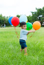 Asian baby boy play with bunch of balloon Royalty Free Stock Photo