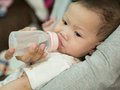 Asian baby eating milk in bottle. Royalty Free Stock Photo