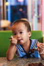Asian baby girl eating chocolate and mouth is dirty Royalty Free Stock Image