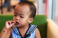 Asian baby girl eating chocolate and mouth is dirty Stock Images
