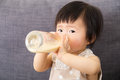 Asian baby girl feed with milk bottle at home Stock Photos
