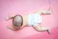 Asian baby girl overturn on pink bed top view of Royalty Free Stock Image