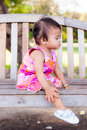 Asian baby girl sitting on bench Royalty Free Stock Photography