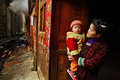 Asian with baby in her arms stands on rural street zengchong village guizhou china april chinese woman child the village near a Stock Photo