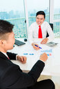 Asian banker counseling financial investment offering client finance assets in bank office Royalty Free Stock Photo