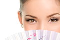 Asian beauty eyes makeup woman looking with fan oriental mysterious chinese lady showing eyeliner and mascara hiding face behind Stock Photography