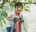 Asian boy climbing on rope pole in playground Royalty Free Stock Photo