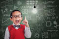 Asian boy has idea under lit bulb in classroom student class with written board Royalty Free Stock Photos