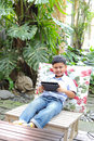 Asian boy playing tablet at the park Royalty Free Stock Photo