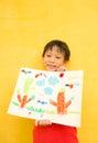 Asian boy smiling displaying his artwork Stock Photos