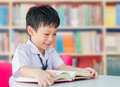 Asian boy student in school library uniform reading book Stock Photography