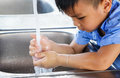 Asian boy is watching her hand with water Royalty Free Stock Photo