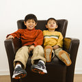 Asian brothers in chair Royalty Free Stock Image
