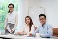 Asian business colleagues sitting at the office table and looking at the camera Royalty Free Stock Photo