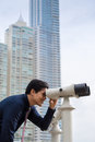 Asian business man with binoculars looking at city portrait of young chinese standing in panama and through concept of forecasting Stock Photo