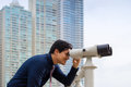 Asian business man with binoculars looking at city portrait of young chinese standing in panama and through concept of forecasting Royalty Free Stock Image