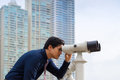 Asian business man with binoculars looking at city portrait of young chinese standing in panama and through concept of forecasting Stock Images