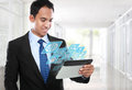 Asian business man using tablet pc and smiling with conceptual image Stock Photos
